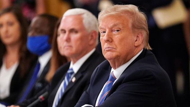 President Trump is seated next to Vice President Mike Pence as he listens during an event on reopening schools amid the coronavirus pandemic in the East Room at the White House in Washington July 7, 2020.