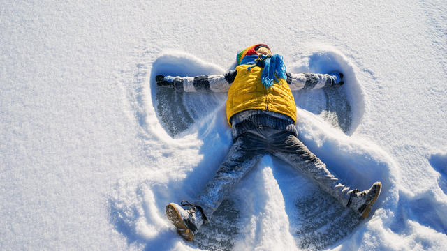 Boy making a snow angel