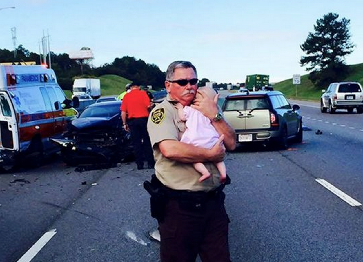Deputy comforts crying baby after traffic accident in