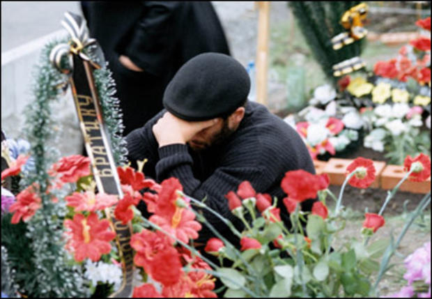 Grief is universal at the Beslan cemetery for victims of the September 2004 siege.