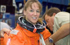Astronaut Lisa M. Nowak, STS-121 mission specialist, dons a training version of the shuttle launch and entry suit