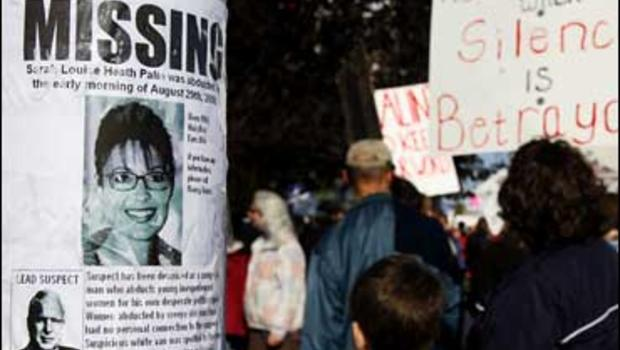 A missing sign with Alaska Gov. Sarah Palin's picture is taped on a light post as protesters hold signs at a Hold Palin Accountable rally