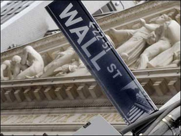 The Wall Street sign is juxtaposed against the sculpture on the facade of the New York Stock Exchange