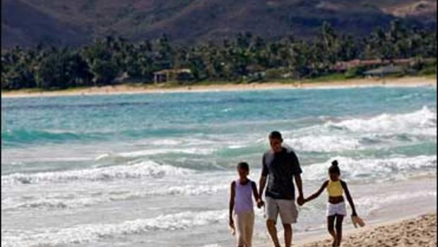 In this Aug. 12, 2008 file photo President-elect Barack Obama walks the beach with his daughters Malia, 10, left, and Sasha, 7, during his vacation in Kailua, Hi. Places that U.S. presidents have called home often become major tourist attractions, from es