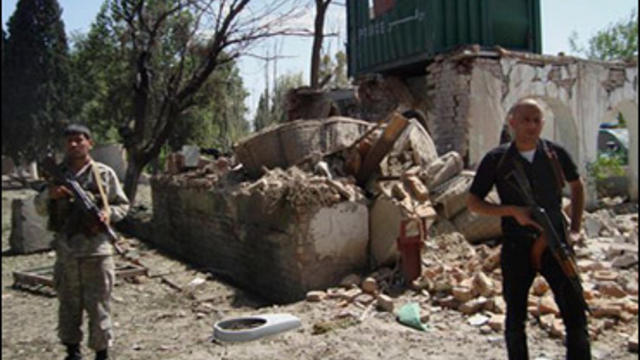 Afghan security men stand near a damaged police check post following attacks on government buildings in Khost