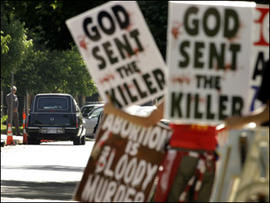 Protesters from Rev. Fred Phelps' Westboro Baptist Church demonstrate during funeral services for Dr. George Tiller Saturday, June 6, 2009, at College Hill United Methodist Church in Wichita, Kan.