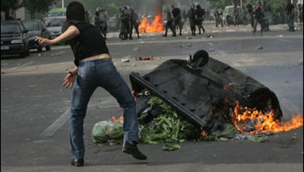 Supporters of opposition leader Mir Hossien Mousavi set fire to a barricade as they hurl stones during a protest in Tehran on Saturday June, 20, 2009.