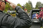 Members of the Patriot Guard salute the flag-draped casket of Brian N. Bradshaw, after it was loaded into a hearse at St. John's Bosco Church in Lakewood, Wash. on Monday, July 6, 2009.