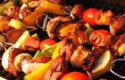 Kebabs cooking on the grill with metal skewers.