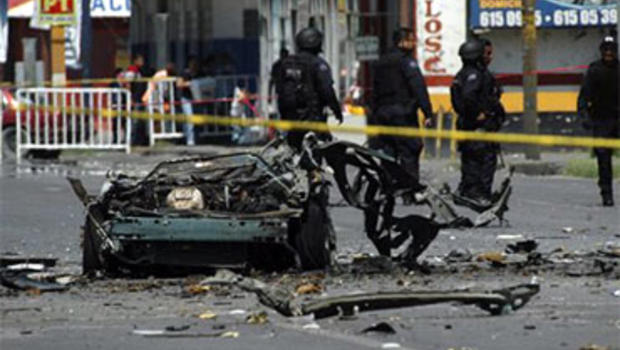 The remains of a vehicle are cordoned off in a street in the northern border city of Ciudad Juarez, Mexico, Friday July 16, 2010. Mexican investigators ran forensic tests to determine whether drug gangs used a car bomb in an attack on police patrol trucks