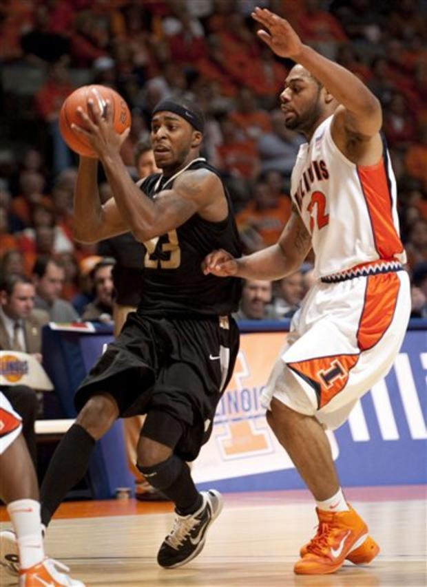 Oakland guard Reggie Hamilton (23) is defended by Illinois guard Demetri McCamey (32).