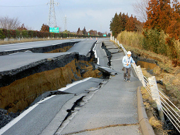 After earthquake in japan, worker examines road.