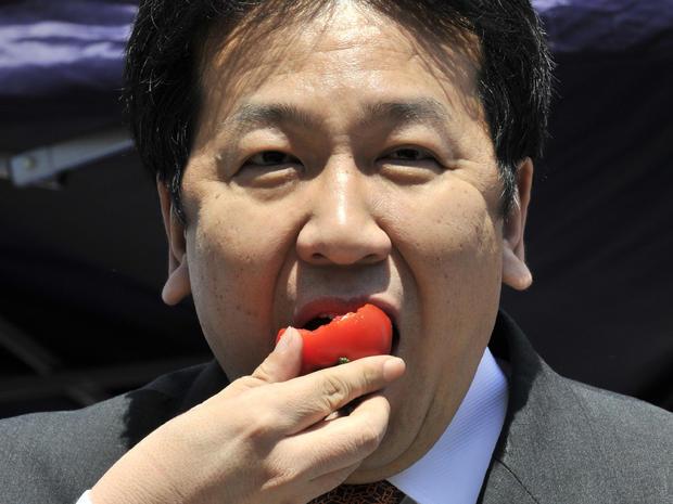 Japan's Chief Cabinet Secretary Yukio Edano eats a tomato