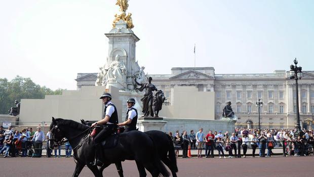 Mounted police patrol past Buckingham Palace