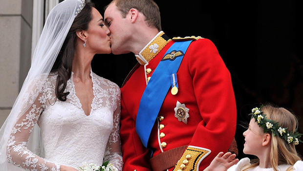 Watched by one of the bridesmaids, Prince William and his wife Kate Duchess of Cambridge, kiss