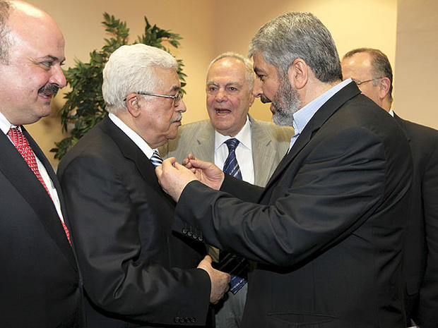 In this photo released by the Hamas Media Office, Palestinian President Mahmoud Abbas, center-left, and Hamas leader Khaled Mashaal, center-right, speak to each other at a ceremony in Cairo, Egypt Wednesday, May 4, 2011.