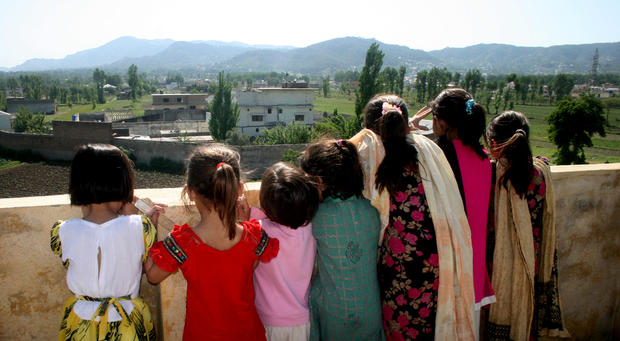 Pakistani children look out from their high vantage point, to see the compound of Osama bin Laden in Abbottabad, Pakistan