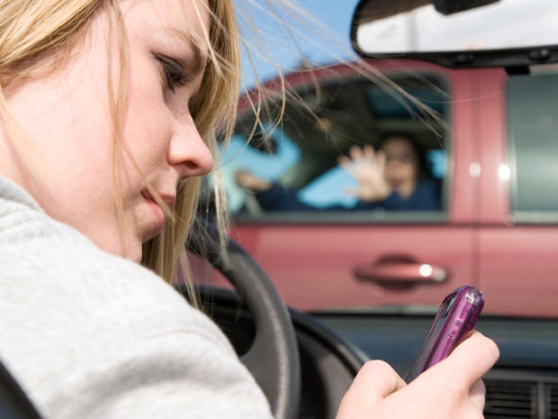 A teenager texting on her phone and looking away from the road