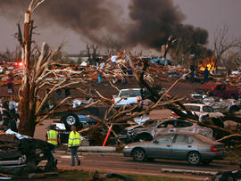 Emergency personnel walk through a neighborhood severely damaged by a tornado