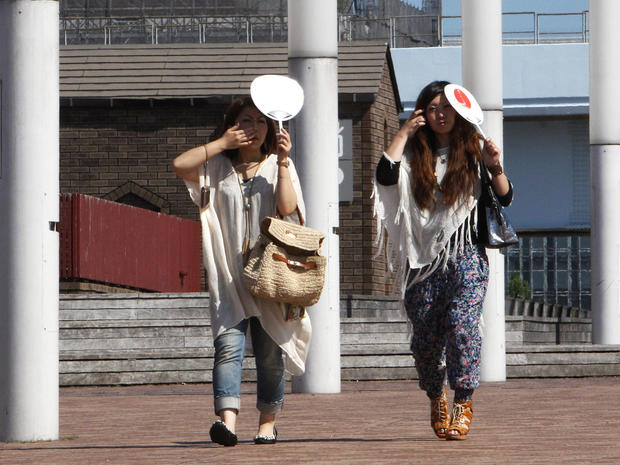 Women shield themselves from Tokyo sun with handheld fans