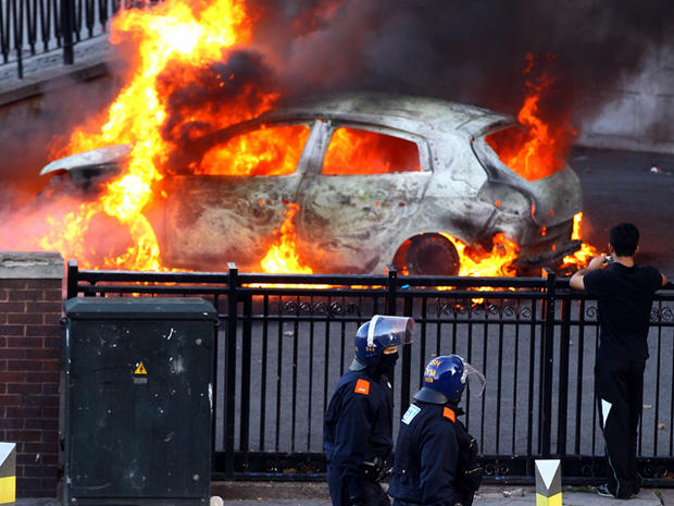 Police walk past a burning car during riots in Birmingham City Centre Aug. 8, 2011, in Birmingham, England. After three nights of rioting and looting in and around London, the chaos is starting to spread to other cities around Britain.