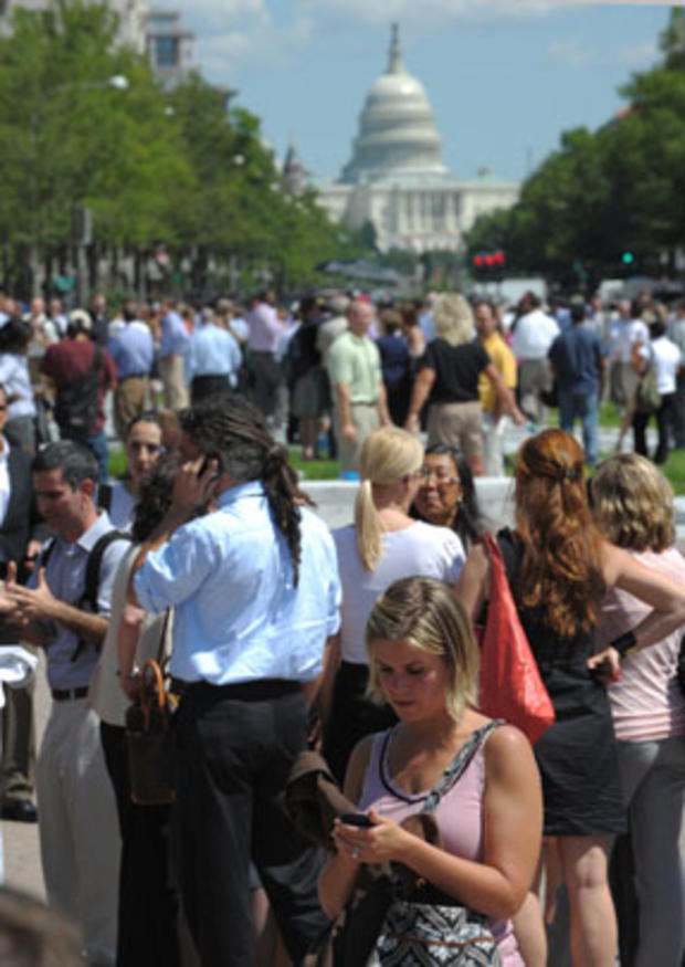 A woman checks her phone as office workers and others gather on Freedom Plaza after an earthquake was felt in Washington D.C. Aug. 23, 2011.