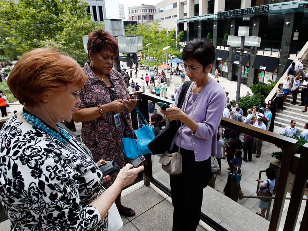 People check their phones as they wait outside of an office building after an earthquake was felt in Baltimore, Tuesday, Aug. 23, 2011.