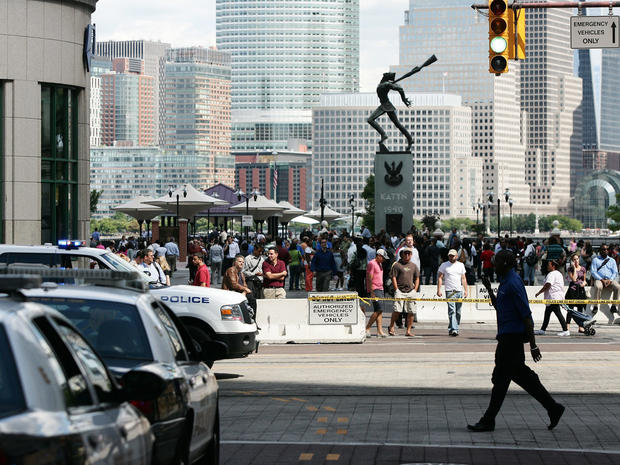 People stand outside after a temporary evacuation from office buildings in Jersey City, N.J., Aug. 23, 2011.