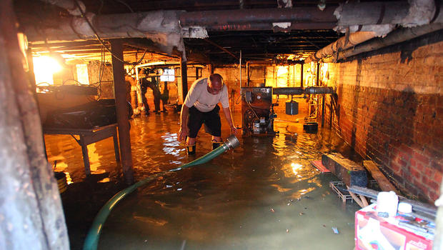 Nick Feola tries to get the gallons of water out of his basement at his home of 32 years on 5th Street in Hoboken, N.J.