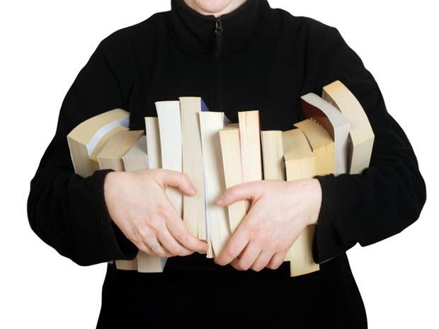 Model holding row of paperback books.