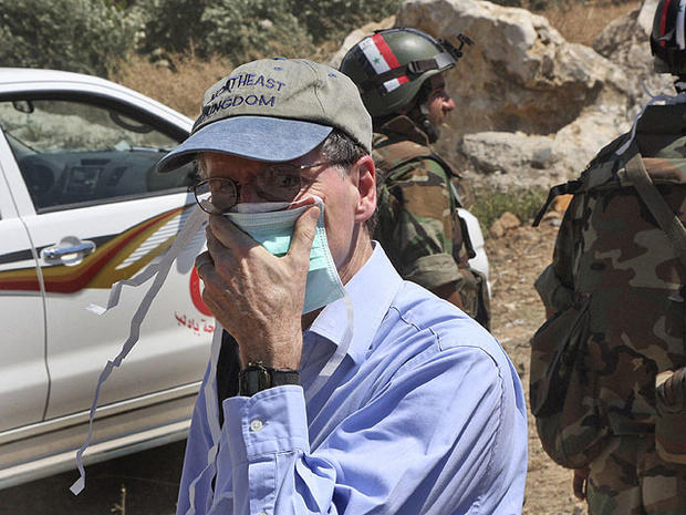 In this June 20, 2011 photo taken during a government-organized tour for foreign diplomats and the media, U.S. ambassador in Syria Robert Ford, covers his nose during his visit with other foreign diplomats to a mass grave, in Jisr el-Shughour, north of Syria.