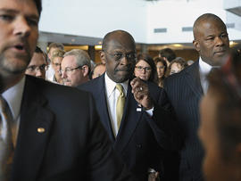 Republican presidential candidate Herman Cain, center, is surrounded by security and staff as he walks through a hotel lobby in Alexandria, Va., Nov. 2, 2011, before speaking after meeting with doctors attending the Docs4PatientCare conference.