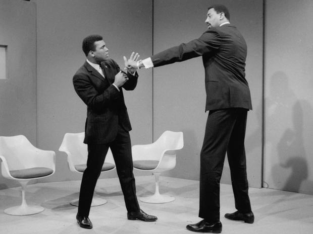 Wilt Chamberlain extends a long left in the direction of Muhammad Ali