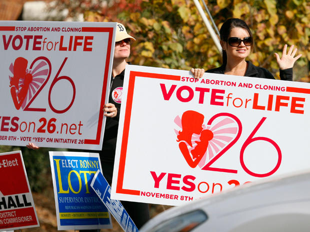 Christi Chandler, left, and Stacy Hawsey, both of Madison and supporters of the Personhood Amendment promote their initiative as they waver signs at drivers in the midst of last minute campaigning Tuesday, Nov. 8, 2011 in Madison, Miss. The Mississippi measure that would define life as beginning at conception was given a decent chance of approval. Passage would be the first victory in the country for the so-called personhood movement, which aims to make abortion all but illegal. Similar attempts have failed in Colorado and are under way elsewhere.