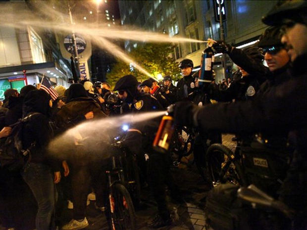 Seattle Police officers deploy pepper spray into a crowd