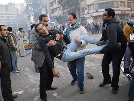 Egyptian men carry a wounded protester during clashes with Egyptian riot police, unseen, in Cairo, Egypt, Nov. 23, 2011.