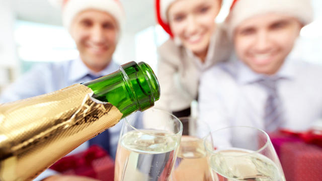 Close-up of bottle of champagne and flutes in the background of business people