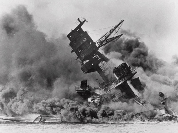 USS Arizona belches smoke as it topples into Pearl Harbor