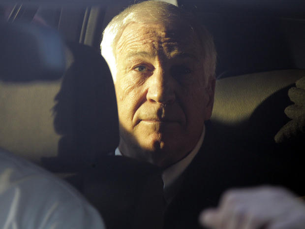 Former Penn State assistant football coach Jerry Sandusky sits in the back seat of his attorney's car as he leaves the Centre County Courthouse in Bellefonte, Pa., Dec. 13, 2011.