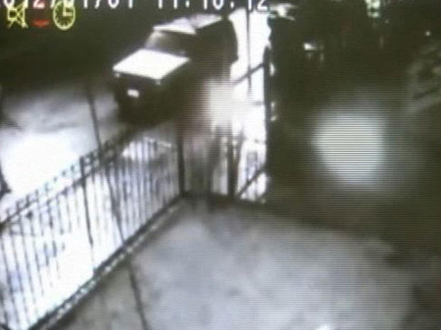 In this frame grab taken from surveillance video released by the NYPD, a suspect, left, throws a lit object at a home in the Queens borough of New York on Sunday night, Jan. 1, 2012.