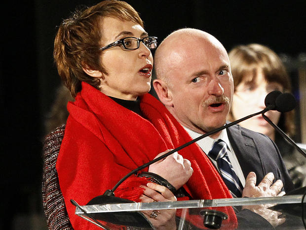 Rep. Gabrielle Giffords leads the Pledge of Allegiance accompanied by her husband, former astronaut Mark Kelly, Jan. 8, 2012, in Tucson, Ariz., at the start of a memorial vigil remembering the victims and survivors one year after the Arizona congresswoman was wounded in a shooting that killed six others.