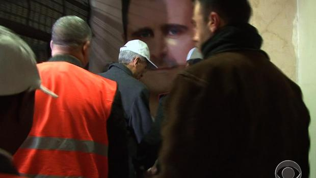 Observers from the Arab League arrive at the Damascus Criminal Justice Headquarters, where the image of Syrian president Bashar al-Assad is prominent on the walls.