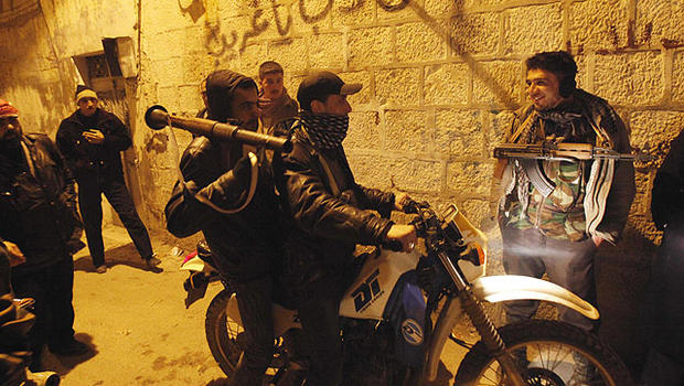 In this Feb. 5, 2012 photo, Syrian rebels gather in an alley as they secure a demonstration in Idlib, Syria.