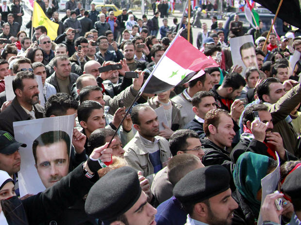 Syrian supporters of President Bashar al-Assad hold his portrait as they wave their national flag during a pro-regime demonstration at Sabe Bahrat Square in Damascus, Syria, Feb. 12, 2012.