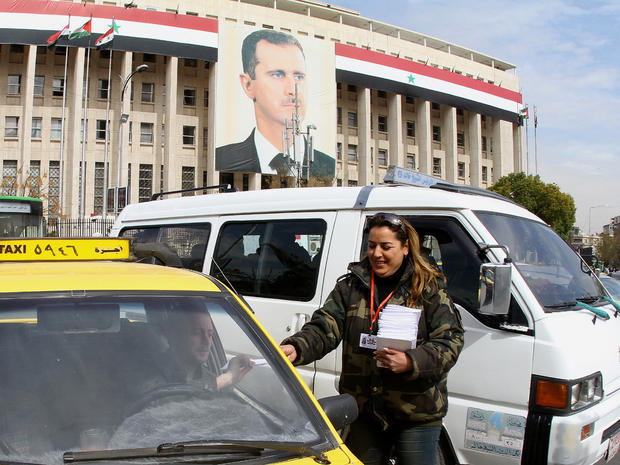 A woman hands a copy of the draft constitution to a taxi driver in Damascus