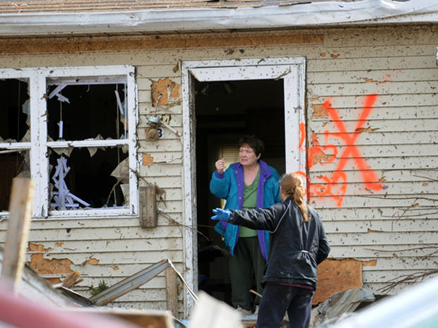 Margaret Shimkus, 61, talks with an emergency responder about her condition Wednesday, Feb. 29, 2012, at her home in Harrisburg, Ill., after an early morning tornado ripped through the town.