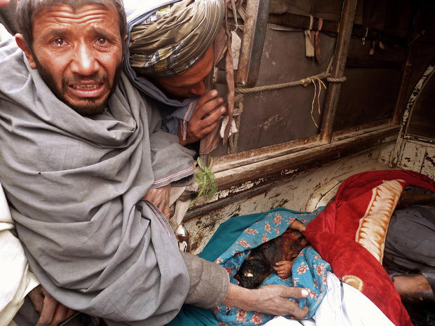A mourner cries over the bodies of Afghan civilians