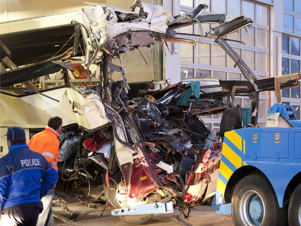 Wreckage of a tourist bus from Belgium is dragged by a tow truck outside a motorway tunnel