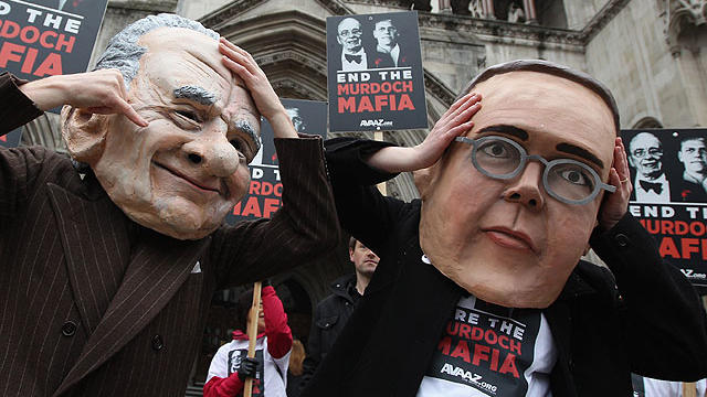 Protesters from the campaign group 'Avaaz' demonstrate outside the High Court with large James and Rupert Murdoch masks as former News International chairman James Murdoch gives evidence to The Leveson Inquiry on April 24, 2012 in London, England.