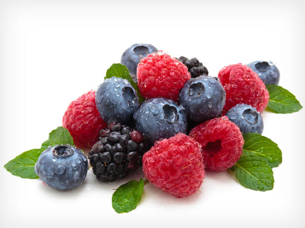 Mix of differrerent berries with mint leaves. Isolated on white.
